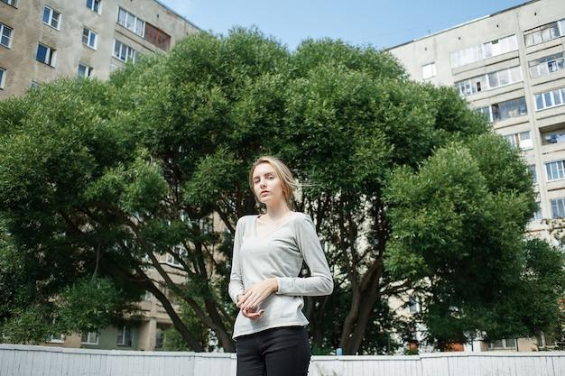 Linda jovem magra caucasiana com longos cabelos loiros ao ar livre em frente a um salgueiro verde