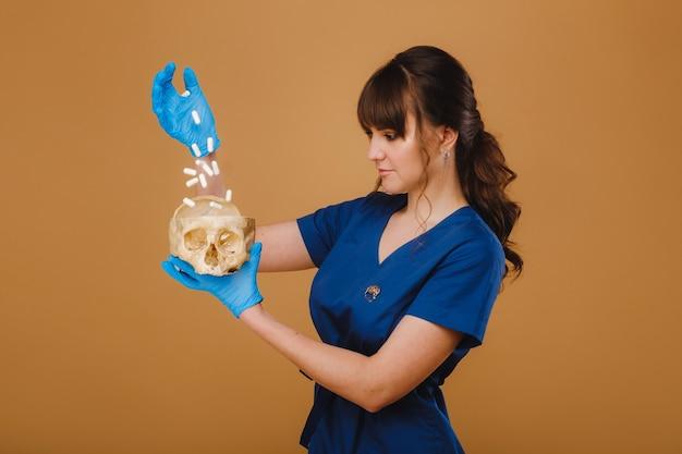 Linda jovem médica segurando um crânio humano, fundo marrom atrás do médico.
