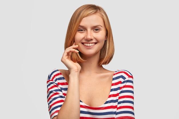 Linda jovem modelo com sorriso gentil, cabelo curto e pele sardenta, mantém a mão perto do rosto