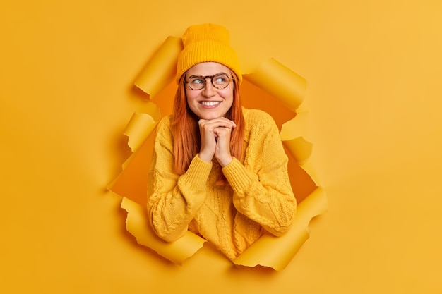 Linda jovem modelo feminina com cabelos ruivos mantém as mãos sob o queixo concentradas de lado e sorri suavemente, veste roupas da moda jovem pensa em planos futuros imagina algo bom em mente.