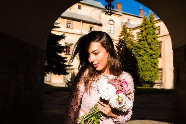Linda jovem modelo segurando um buquê de flores. mulher posando para a rua com sombra no rosto