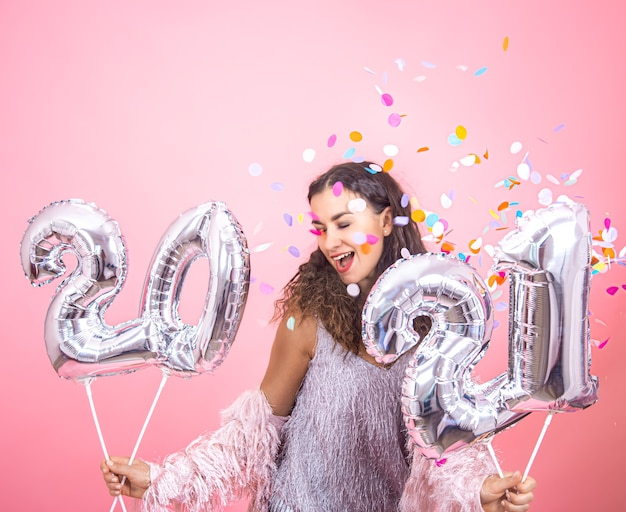 Linda jovem morena com cabelo encaracolado e roupas festivas, dançando com confete no rosto e segurando balões de prata para o conceito de ano novo