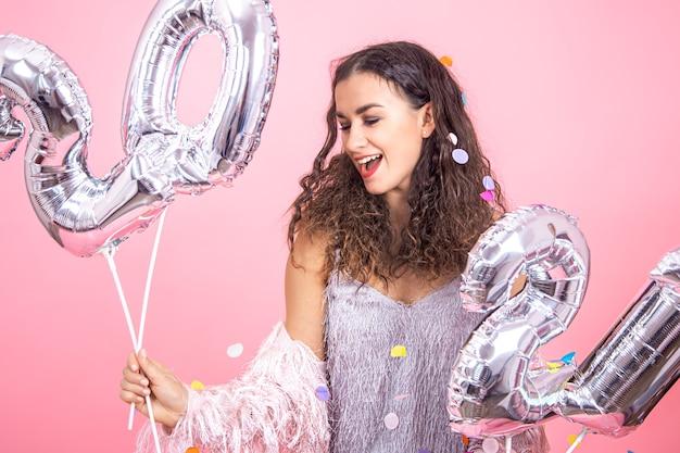 Linda jovem morena com cabelos cacheados e roupas festivas, posando em um fundo rosa de estúdio com confete e segurando balões de prata para o conceito de ano novo