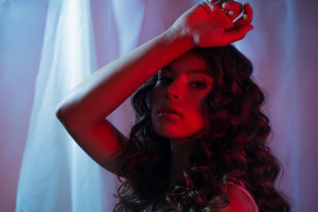 Linda jovem morena com cabelos cacheados, retrato em luz neon, vermelho brilhante