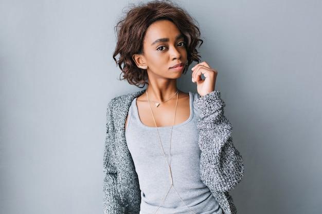 Linda jovem morena com penteado curto e encaracolado na parede cinza. vestindo roupas casuais - casaco de lã cinza, jaqueta de malha, camisa, colar longo e elegante com triângulo.