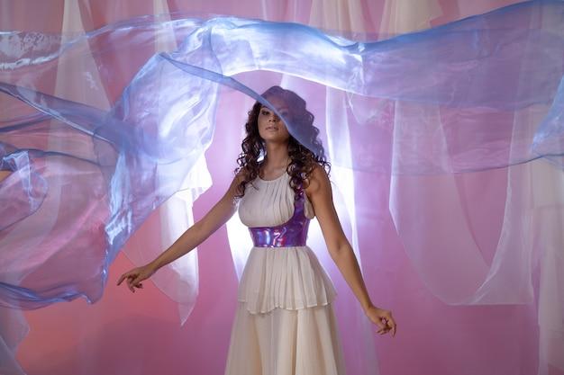 Linda jovem morena com um vestido longo branco leve de tecido voador