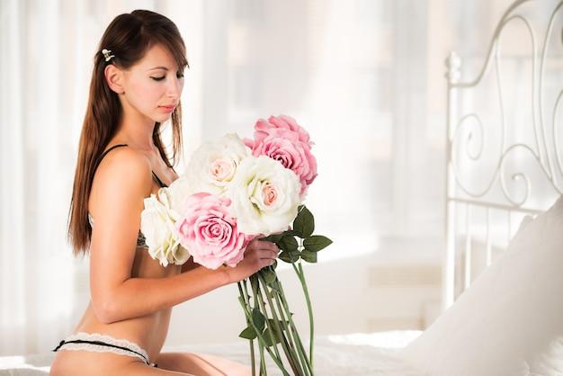 Linda jovem morena de cueca sexy preta, deitada na cama e segurando uma flor