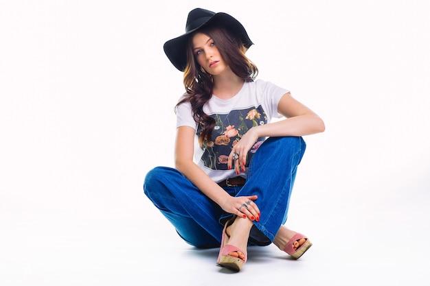 Linda jovem morena de jeans com camiseta branca de boca de sino e chapéu preto, sentada no chão