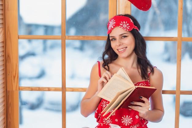 Linda jovem morena de pijama vermelho e lendo pela janela