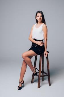 Linda jovem morena de saia preta curta sentada em uma cadeira alta de madeira isolada no branco