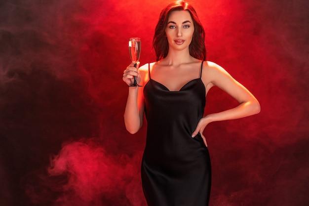 Linda jovem morena de vestido preto segurando uma taça de champanhe.