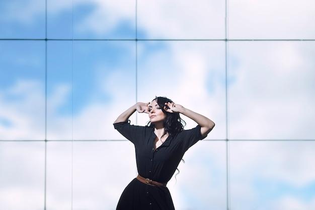 Linda jovem morena em um vestido preto perto da grande janela do escritório
