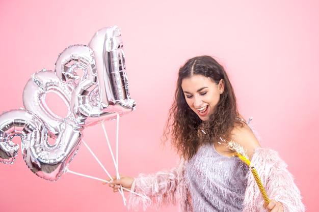 Linda jovem morena emocional com cabelos cacheados vestida festivamente segurando uma vela de fogos de artifício na mão e balões prateados para o conceito de ano novo em uma parede rosa
