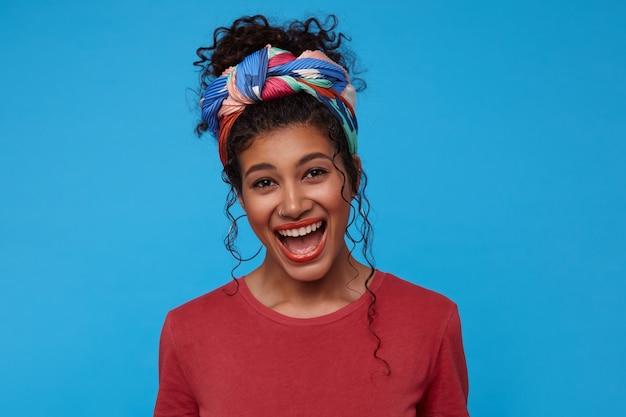 Linda jovem morena encaracolada, muito feliz, vestida com uma camiseta cor de vinho e uma faixa colorida, mantendo a boca aberta enquanto ria alegremente, isolada sobre a parede azul