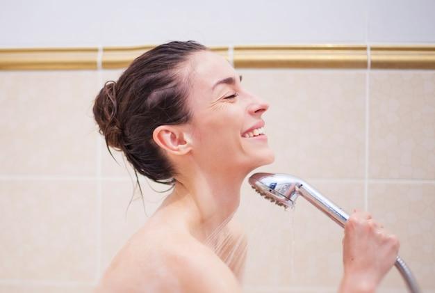 Linda jovem morena está realizando o banho em casa