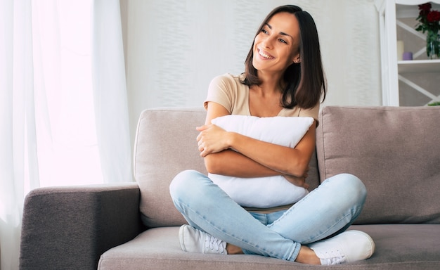 Linda jovem morena feliz relaxando no sofá em casa e sonhando