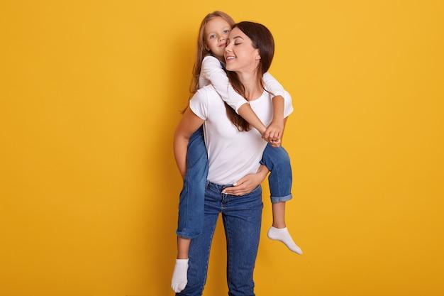 Linda jovem morena mãe segura sua filha loira bonitinha na camisa branca e macacão