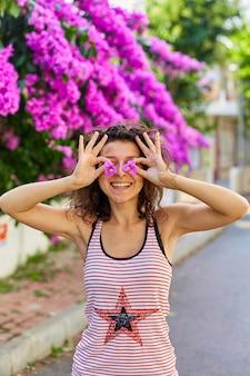 Linda jovem morena modelo posando com flores roxas desabrochando na turquia, na ilha de buyukada