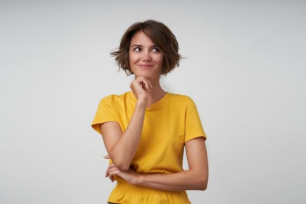 Linda jovem morena satisfeita com um penteado casual, apoiando o queixo na mão levantada e olhando para o lado positivamente, posando com uma camiseta amarela