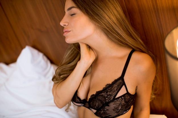 Linda jovem morena sentada na cama no quarto em casa