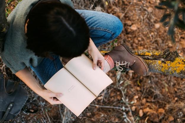 Linda jovem morena sentada nas folhas de outono caídas em um parque, lendo um livro