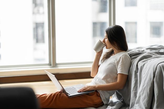 Linda jovem morena trabalhando em um laptop e tomando café, sentada no chão perto da cama pela janela panorâmica