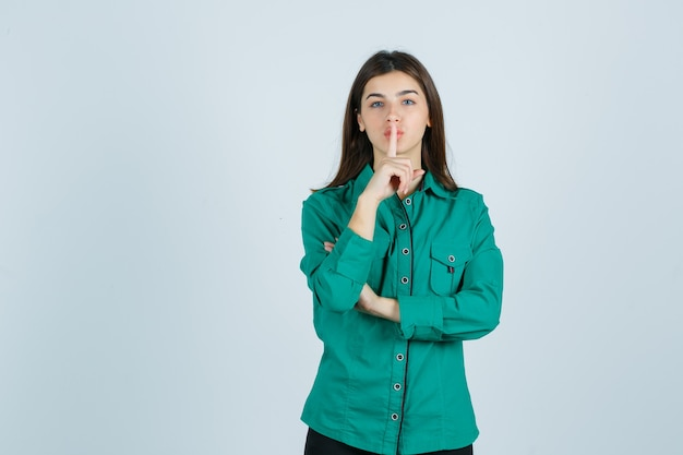 Linda jovem mostrando o gesto de silêncio na camisa verde e olhando com cuidado. vista frontal.