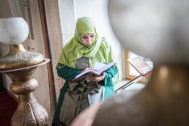 Linda jovem muçulmana dentro da mesquita lendo o livro sagrado do alcorão
