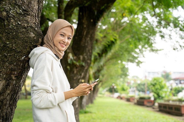 Linda jovem muçulmana sorridente usando o telefone celular durante a pausa para exercícios ao ar livre