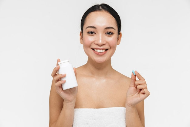 Linda jovem muito asiática com pele saudável posando nua isolada sobre uma parede branca, segurando a pílula de vitaminas.