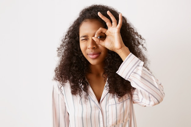 Linda jovem mulata com pele bronzeada brilhante e penteado encaracolado bagunçado sorrindo pelo buraco entre o polegar e o indicador como se estivesse usando binóculos