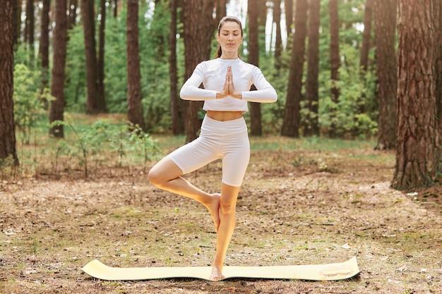Linda jovem mulher adulta com rabo de cavalo vestindo blusa branca e leggins em pé no karemat em pose de árvore, fazendo ioga sozinha na floresta, curtindo a natureza e o ar fresco.