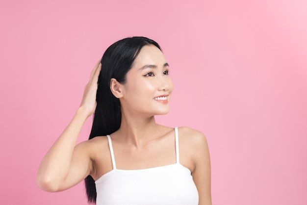 Linda jovem mulher asiática cuidando do cabelo dela.