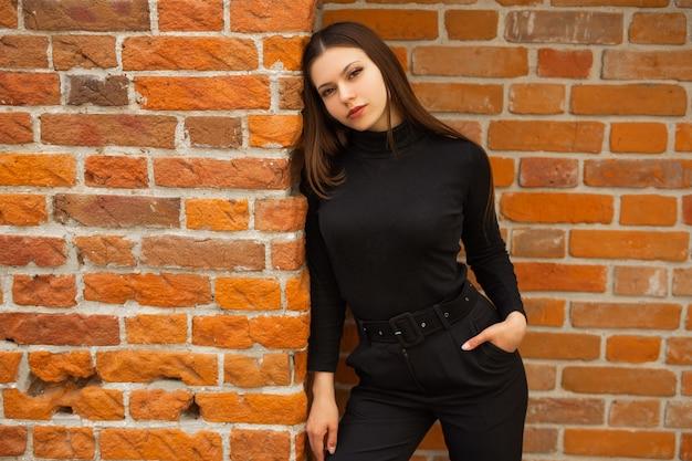 Linda jovem mulher com roupas pretas sobre um fundo de parede de tijolos
