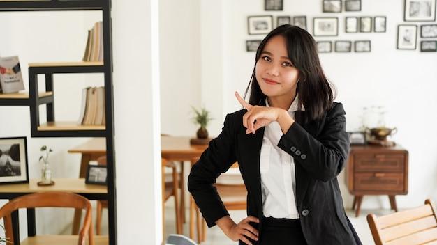 Linda jovem mulher de negócios asiática de terno e mãos apontando o dedo para cima no escritório