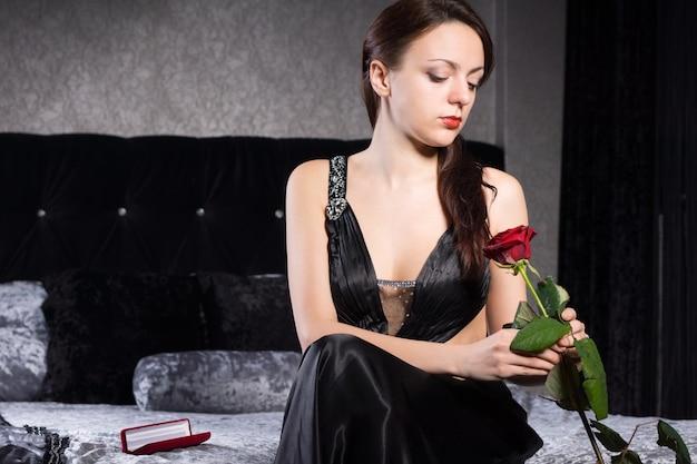 Linda jovem mulher de vestido preto, sentado no quarto, segurando uma flor rosa vermelha.