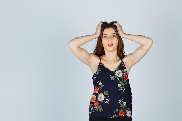 Linda jovem mulher segurando a blusa com as mãos na cabeça e parecendo animada