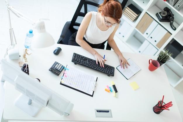 Linda jovem no escritório trabalhando com documentos, calculadora, bloco de notas e computador