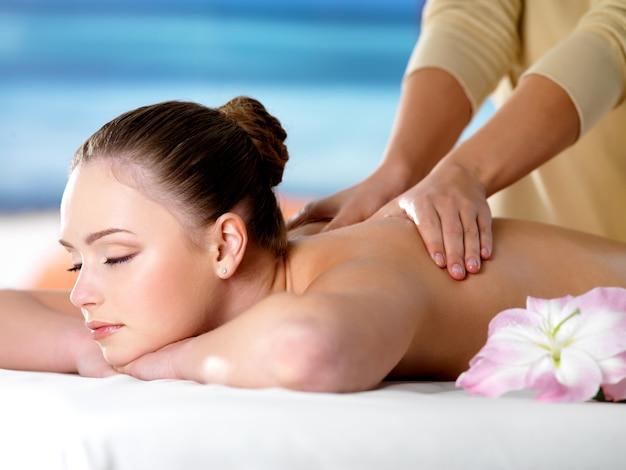 Linda jovem no salão de beleza recebendo massagem no spa