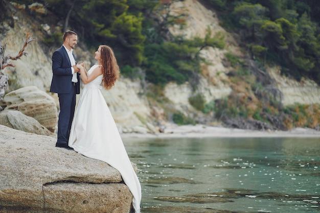 Linda jovem noiva cabelos compridos em vestido branco com seu jovem marido perto do rio
