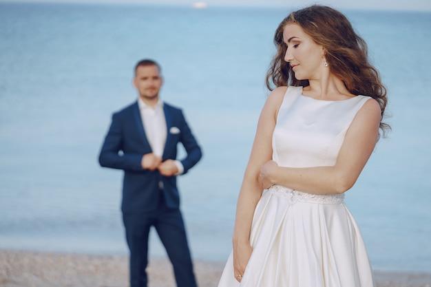 Linda jovem noiva cabelos longos em vestido branco com seu jovem marido na praia