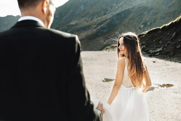Linda jovem noiva caucasiana levando seu noivo de mãos dadas e olhando para ele caminhando na montanha no dia do casamento.