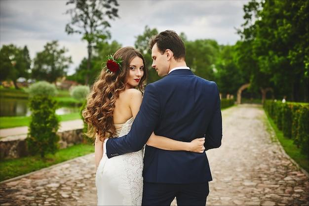 Linda jovem noiva com penteado de casamento decorado com flores e abraços com seu lindo noivo