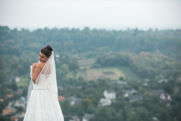 Linda jovem noiva posa para a câmera na cidade à distância