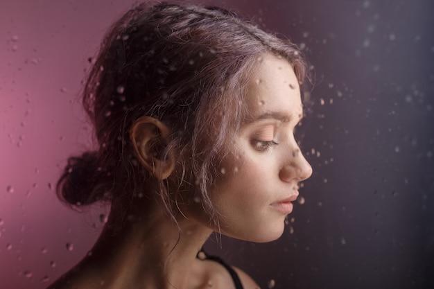 Linda jovem olha para baixo sobre fundo roxo. gotas borradas de água escorrem pelo vidro na frente de seu rosto