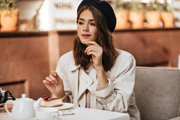 Linda jovem parisiense com penteado escuro ondulado, lábios vermelhos, boina, sobretudo bege, sentada no terraço do café da cidade, tomando cheesecake e chá, olhando para longe