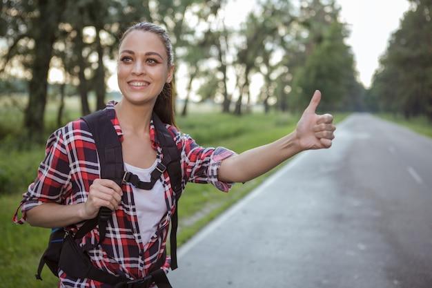 Linda jovem pedindo carona na zona rural