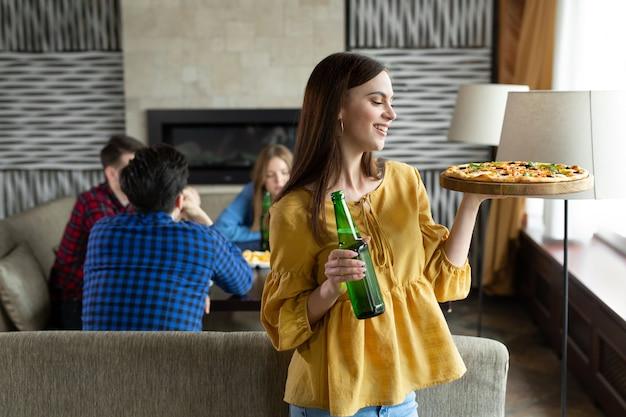 Linda jovem posa com cerveja e pizza em um café