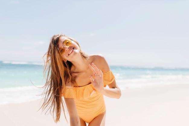 Linda jovem posando emocionalmente com as ondas do mar e o horizonte. garota muito morena de óculos escuros e maiô laranja, expressando felicidade.