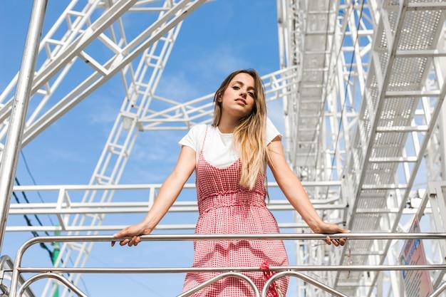 Linda jovem posando no parque de diversões